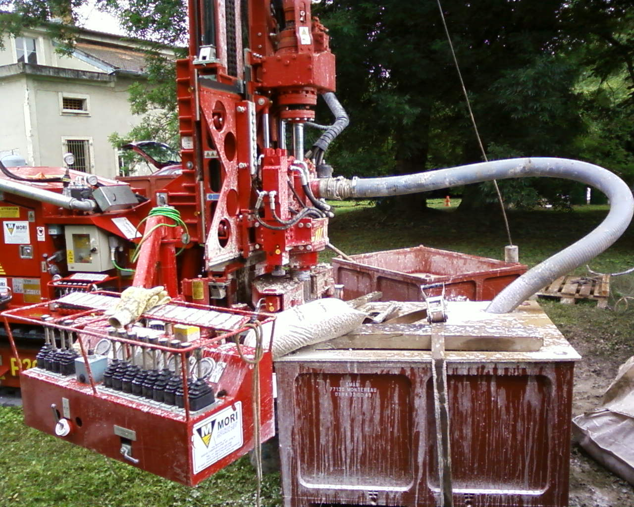 Drilling machine with 2 heads. The first turns right to drive the tool. The second is a hollow shaft head which drives the casing and turns to the left. A collecting device is placed between the two heads to collect the cuttings and to not pollute the environment of the drilling site. A high-frequency vibrating hammer is placed on the side of the swing out carriage to take undisturbed samples in the center of the borehole.